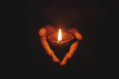 Hands holding a small candle