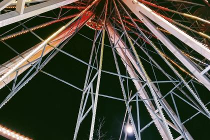 A lit up Ferris wheel at night.