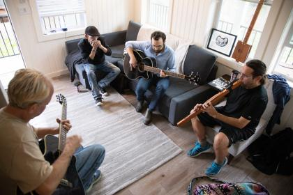 Four men sit in a room playing instruments.