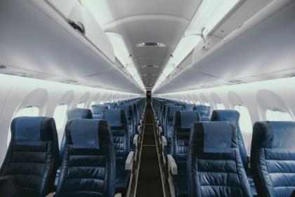 The inside of an empty airplane with blue seats.