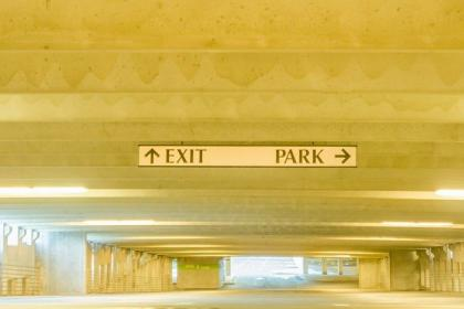 An empty parking garage with signs saying Park and Exit.