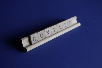 Scrabble tiles form the word CONTACT.